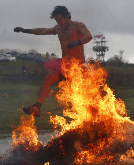A competitor jumps across a burning obstacle during the Tough Guy event in Perton, central England January 26, 2014. The annual event to raise cash for charity challenges thousands of international competitors in a cross country run followed by an assault course consisting of obstacles including water, fire and tunnels. (Darren Staples/Reuters)
