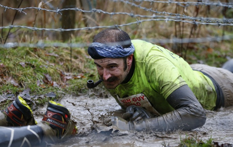 A competitor smokes a pipe as he crawls under barbed wire during the Tough Guy event in Perton, central England, January 26, 2014. The annual event to raise cash for charity challenges thousands of international competitors in a cross country run followed by an assault course consisting of obstacles including water, fire and tunnels. (Darren Staples/Reuters)