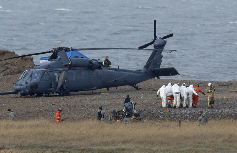 A body is carried away from the scene of a helicopter crash on the coast near the village of Cley next the Sea in Norfolk, eastern England January 9, 2014. British police said on Wednesday they would be working with the U.S. Air Force and others to find out why a U.S. military helicopter crashed on the coast of eastern England, killing all four crew on board. The helicopter, a Pave Hawk assigned to the 48th Fighter Wing based at RAF Lakenheath air base, was performing a low-level training mission along the Norfolk coast when it went down in marshland on Tuesday evening. The helicopter pictured is not the crashed helicopter but a second helicopter, which had been taking part in the same training exercise as the one that crashed. (REUTERS/Luke MacGregor)