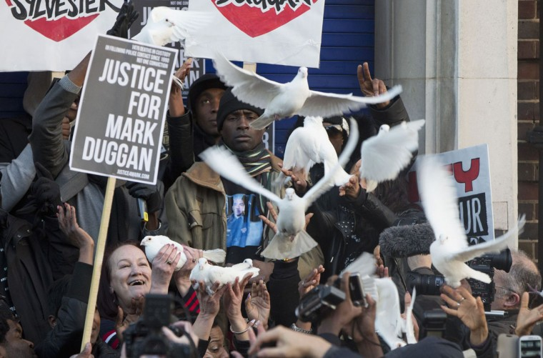 Family members of Mark Duggan, including the mother Pamela (L), release doves during a vigil for him outside Tottenham Police Station in Tottenham, north London January 11, 2014. The vigil followed an inquest that found on Wednesday that police acted lawfully when they shot and killed Mark Duggan whose death sparked a wave of rioting in 2011 in the worst civil unrest in the country in decades. (REUTERS/Neil Hall)
