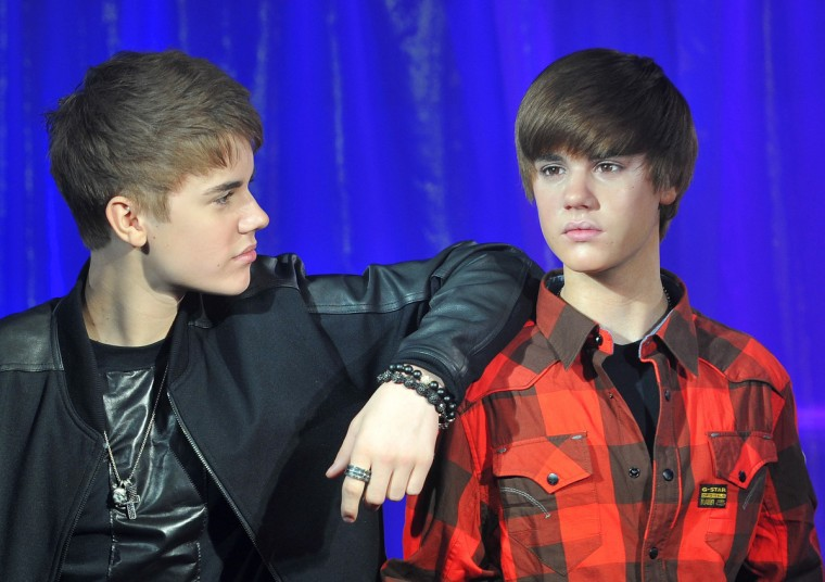 Canadian singer Justin Bieber (black top) poses with a waxwork model of himself during an official unveiling at Madame Tussauds wax museum in central London March 15, 2011. (Toby Melville/Reuters)