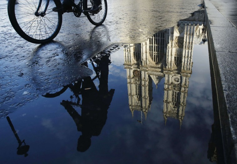 A cyclist is reflected in a puddle as he passes Westminster Abbey in London January 17, 2014. REUTERS/Luke MacGregor