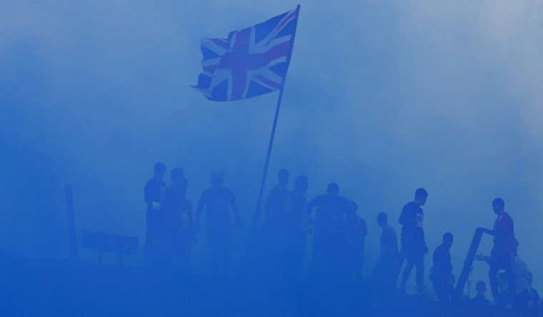 Competitors pass a Union flag as they run through clouds of blue smoke during the Tough Guy event in Perton, central England, January 26, 2014. The annual event to raise cash for charity challenges thousands of international competitors in a cross country run followed by an assault course consisting of obstacles including water, fire and tunnels. (Darren Staples/Reuters)