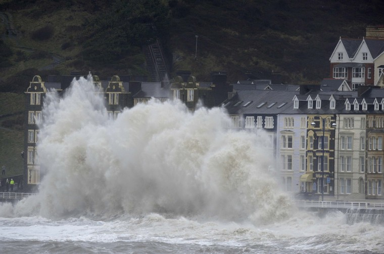 Large waves crash over the promenade at high tide in Aberystwyth, mid Wales January 6, 2014. (Rebecca Naden/Reuters)