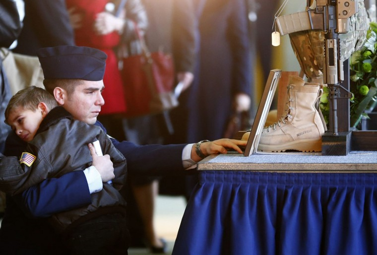 Andy Ponce kneels in front of the weapon, equipment and uniform of his wife, Staff Sgt Afton Ponce, who died in a helicopter accident, after a memorial service at RAF Lakenheath in eastern England January 17, 2014. Andy Ponce is holding their son. A U.S. military helicopter crashed on the coast of eastern England, killing all four crew on board on January 7, 2014. REUTERS/Darren Staples