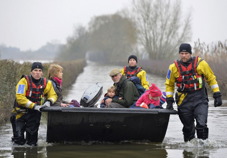 A boat operated by emergency services personnel carries local residents along a flooded road from the village of Muchelney on the Somerset Levels, near Langport in south west England January 30, 2014. Surrounded by flood water, Muchelney has only been accessible by boat for several weeks. British military are on standby to be drafted into the Somerset area to help. REUTERS/Toby Melville
