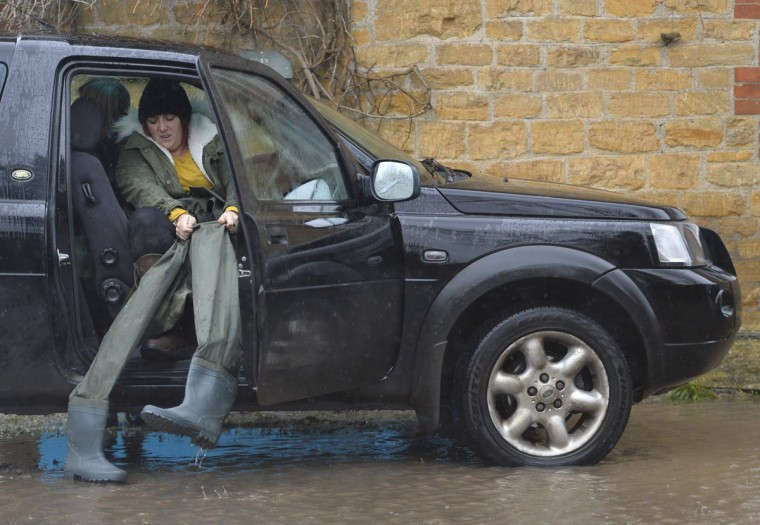 A resident puts on her wader boots as she prepares to walk through flood water in the village of Thorney on the Somerset Levels, near Langport in south west England January 31, 2014. British military are on standby to be drafted into the Somerset area to help. Large areas of the county has been underwater for nearly a month. (REUTERS/Toby Melville)