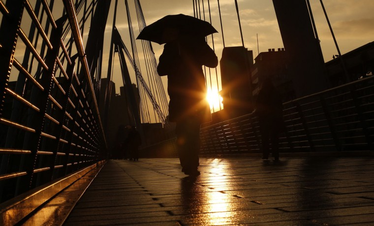 A pedestrian carries an umbrella as he walks over the Hungerford Bridge in London January 31, 2014. (REUTERS/Suzanne Plunkett)