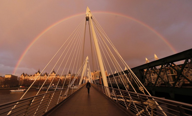 A rainbow appears as a pedestrian crosses the Hungerford Bridge in London January 31, 2014. (REUTERS/Suzanne Plunkett)