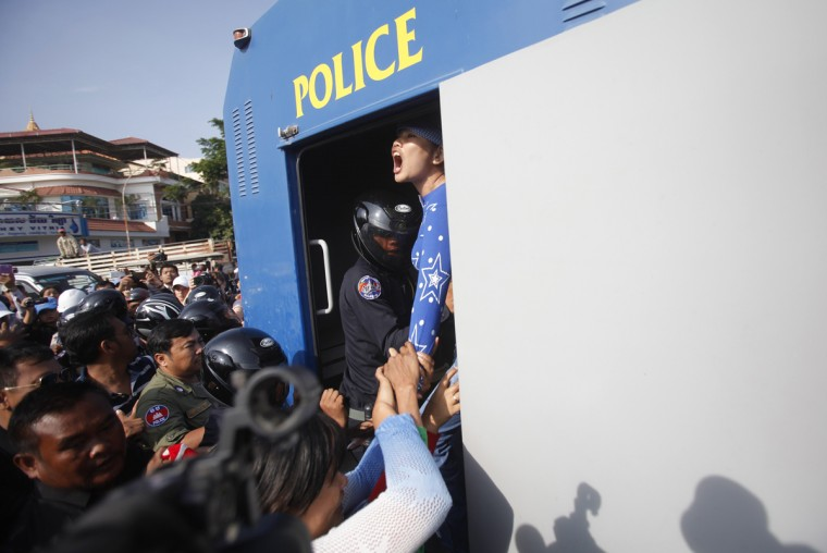 A protester is detained during an attempt to deliver a petition, near the French embassy, in Phnom Penh January 21, 2014. Eleven protesters, including Cambodian activists Yorm Bopha and Tep Vanny, were detained while trying to deliver petitions to foreign embassies in Phnom Penh, calling for help in securing the release of 23 men who were jailed for joining a strike earlier this month over garment factory wages, according to local rights groups. (Samrang Pring/Reuters)