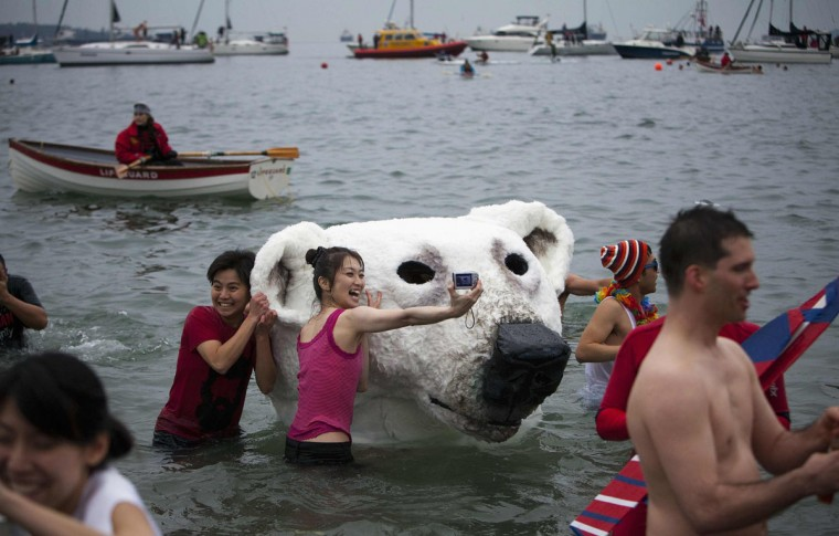 People pose next to a polar bear costume worn by two participants in English Bay during the 94th annual New Year's Day Polar Bear Swim in Vancouver, British Columbia on January 1, 2014. (REUTERS/Ben Nelms)