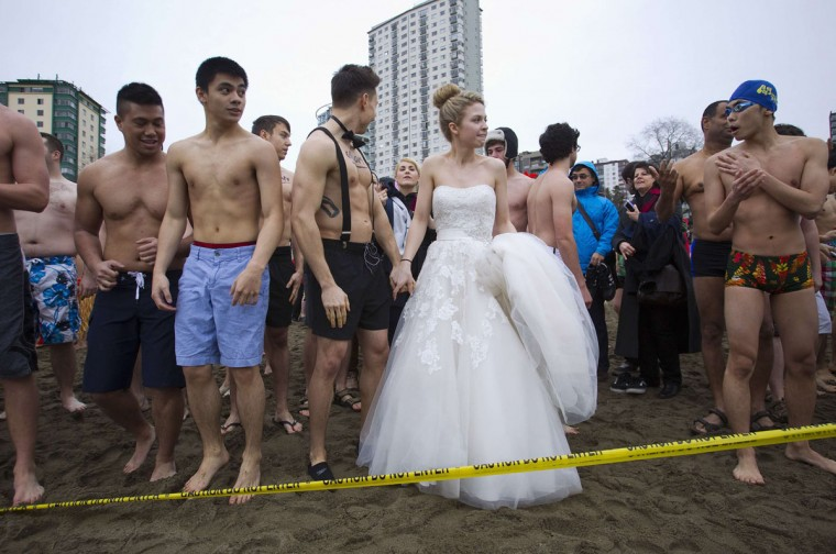 A woman wearing a wedding dress prepares to run into English Bay during the 94th annual New Year's Day Polar Bear Swim in Vancouver, British Columbia on January 1, 2014. (REUTERS/Ben Nelms)