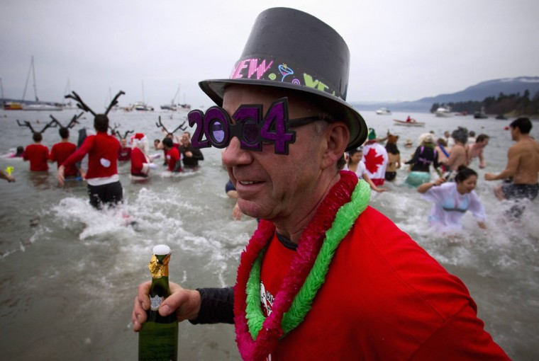 Participants run into English Bay during the 94th annual New Year's Day Polar Bear Swim in Vancouver, British Columbia on January 1, 2014. (REUTERS/Ben Nelms)