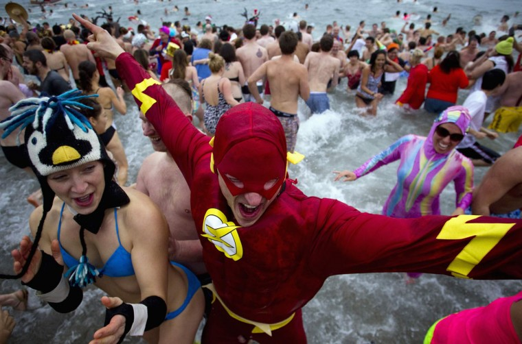 People pose next to a polar bear costume worn by two participants while running into English Bay during the 94th annual New Year's Day Polar Bear Swim in Vancouver, British Columbia on January 1, 2014. (REUTERS/Ben Nelms)