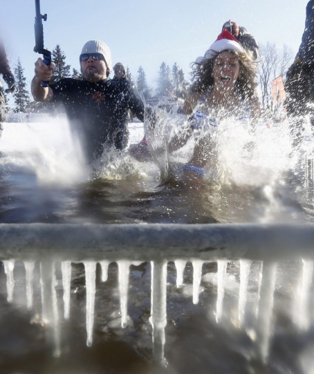 Participants jump into a hole cut in the ice on the Ottawa River during the annual Great Canadian Chill polar bear dip in Ottawa on January 1, 2014. (REUTERS/Chris Wattie)