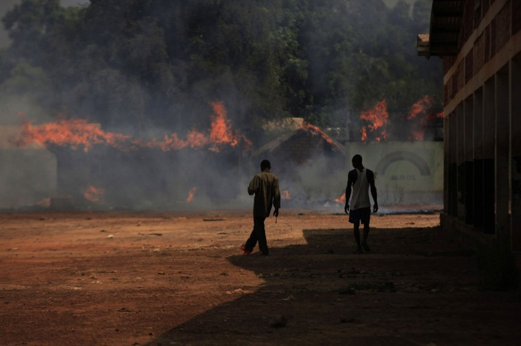 Youths walk towards burning houses in Bossangoa, north of Bangui January 2, 2014. Clashes between Muslims and Christians in Central African Republic's capital killed at least three on Wednesday as angry residents threw grenades and torched homes, witnesses said. (REUTERS/Andreea Campeanu)