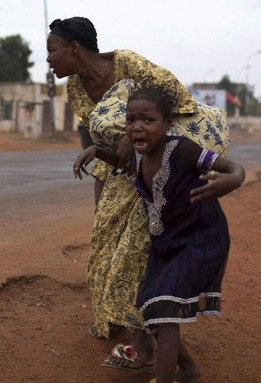 A mother holds her child while attempting to take cover as repeated gun shots are heard close to Miskine district during continuing sectarian violence in the capital Bangui January 28, 2014. At least 13 people were killed in Central African Republic on Monday as the top U.N. human rights official warned of escalating reprisals against Muslims and urged foreign governments to do more to stop the country being torn apart. (Siegfried Modola/Reuters)