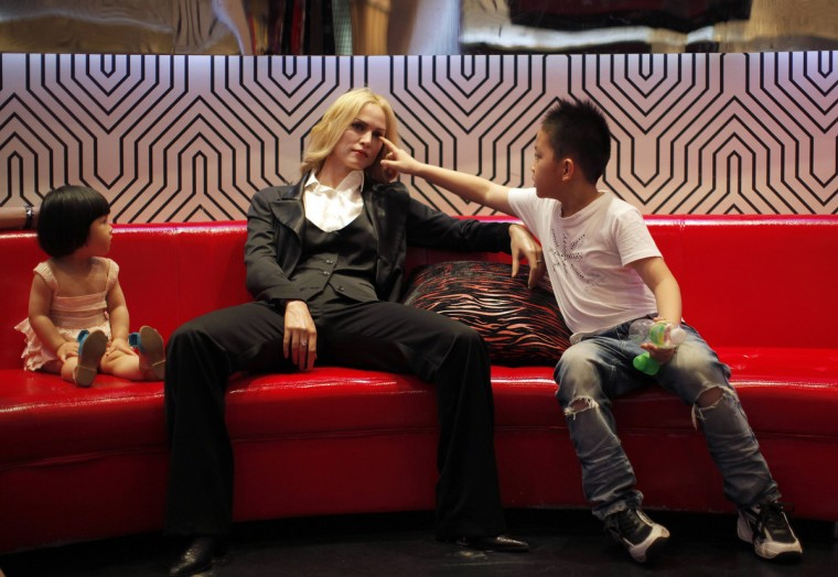Kids sit next a wax statue of pop singer Madonna at the Madame Tussauds Wax Museum in Shanghai July 8, 2011. (Carlos Barria/Reuters)