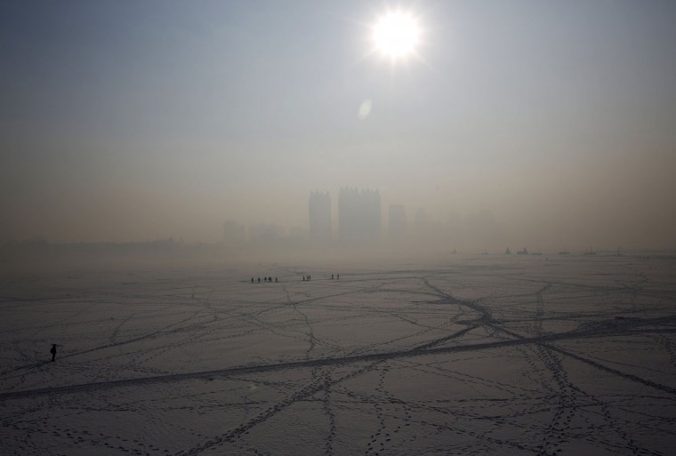 A view of Harbin surrounded by fog is seen over the frozen Songhua River in the northern city of Harbin, Heilongjiang province January 4, 2014. (REUTERS/Kim Kyung-Hoon)