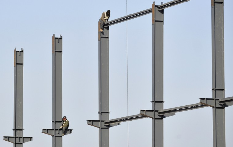 Laborers install steel frames to a new food factory in Taiyuan, Shanxi province. China's annual economic growth likely slowed a touch in the fourth quarter, a Reuters poll showed, confirming market views that the world's second-largest economy lost some vigor at the end of the year as Beijing shifts its focus to reforms. (Jon Woo/Reuters)