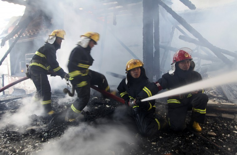 Firefighters spray water as they try to extinguish a fire at the Dukezong Ancient Town in Shangri-la county, Yunnan province January 11, 2014. Fire-fighters extinguished a blaze which destroyed much of an ancient resort town in southwest China on Saturday. It destroyed over 100 houses and incurred a loss of around 100 million yuan ($16.5 million U.S. dollars), local authorities estimated, state media reported. (REUTERS/China Daily)