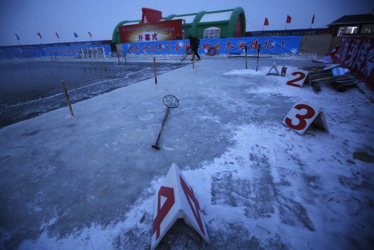 A worker breaks ice on a pool carved into the thick ice covering the Songhua River in the early morning as he prepares the Harbin Ice Swimming Competition in the northern city of Harbin, Heilongjiang province, China on January 5, 2014. According to organizers, about 700 swimmers across China took part in the event on the official launch day of the Harbin Ice and Snow Sculpture Festival. (Kim Kyung-Hoon/Reuters)