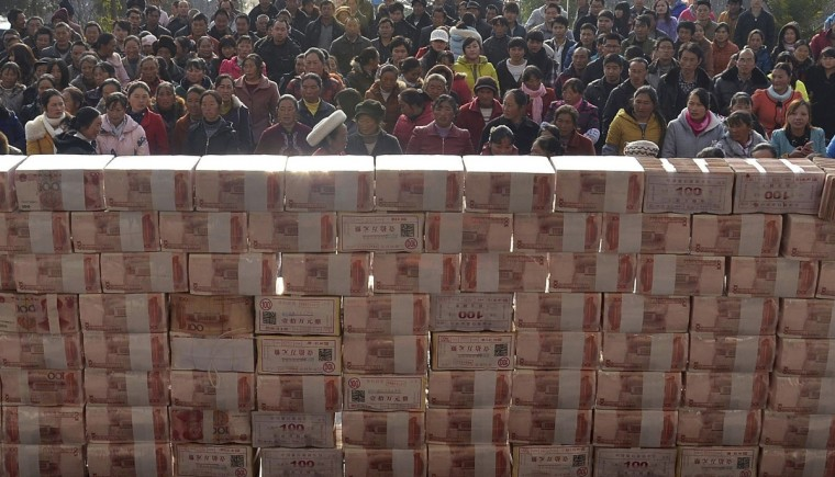 Villagers wait to collect their year-end bonus at Jianshe village, Liangshan, Sichuan province. About 13,115,000 yuan ($2,169,221) were placed in the middle of a square before being distributed as bonus to around 340 villagers in return for their investment in the planting and breeding co-operative in the village in 2013. (Reuters)
