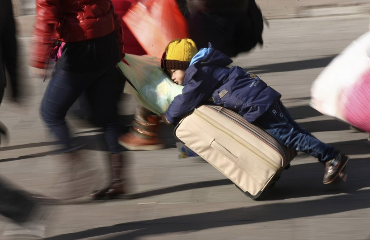 A person drags a suitcase as a boy clings to it on a square in front of a railway station ahead of the Chinese Lunar New Year in Qingdao, Shandong province. About 3.62 billion trips will be made during the 40-day Spring Festival travel rush, which started from January 16, reported Xinhua News Agency citing a government official. (China Daily/Reuters)