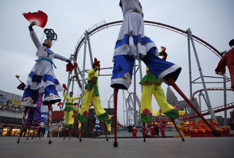 Folk artistes on stilts dance during a folk art performance to celebrate the traditional Chinese Spring Festival on the first day of the Chinese Lunar New Year, which welcomes the Year of the Horse, at the Happy Valley amusement park in Beijing January 31, 2014. (REUTERS/Kim Kyung-Hoon)