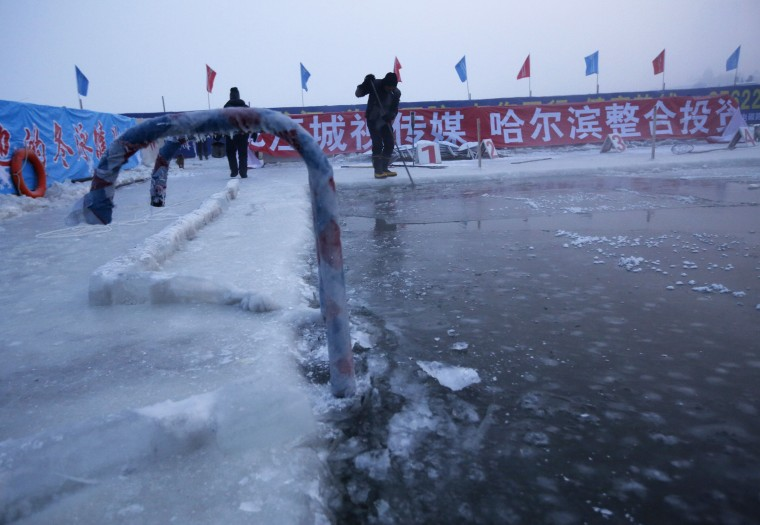 A worker breaks ice on a pool carved into the thick ice covering the Songhua River in the early morning as he prepares the Harbin Ice Swimming Competition in the northern city of Harbin, Heilongjiang province, China on January 5, 2014. (Kim Kyung-Hoon/Reuters)