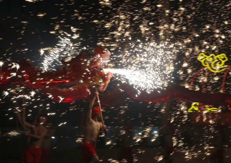 Dancers perform a fire dragon dance in the shower of molten iron spewing firework-like sparks during a folk art performance to celebrate traditional Chinese Spring Festival on the first day of the Chinese Lunar New Year, which welcomes the Year of the Horse, at the Happy Valley amusement park in Beijing January 31, 2014. (REUTERS/Kim Kyung-Hoon)
