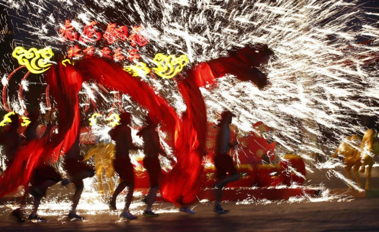 Dancers perform a fire dragon dance in the shower of molten iron spewing firework-like sparks during a folk art performance to celebrate the traditional Chinese Spring Festival on the first day of the Chinese Lunar New Year, which welcomes the Year of the Horse, at the Happy Valley amusement park in Beijing January 31, 2014. (REUTERS/Kim Kyung-Hoon)