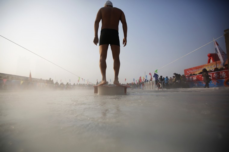A swimmer stands on a platform on a pool carved into the thick ice covering the Songhua River during the Harbin Ice Swimming Competition in the northern city of Harbin, Heilongjiang province, China on January 5, 2014. (Kim Kyung-Hoon/Reuters)
