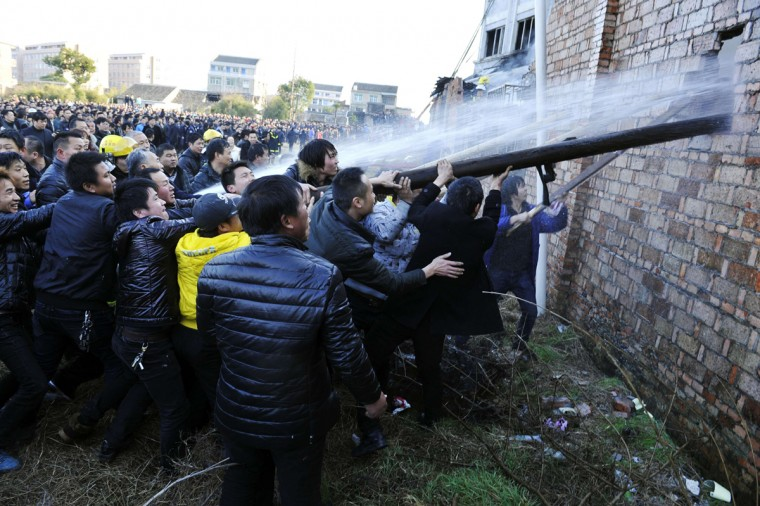 People try to break through the wall for firefighters to extinguish a fire at a factory in Wenling, Zhejiang province, January 14, 2014. According to Xinhua News Agency, the factory fire on Tuesday afternoon killed at least 16 people and an initial investigation of the accident is under way. (Stringer/Reuters)
