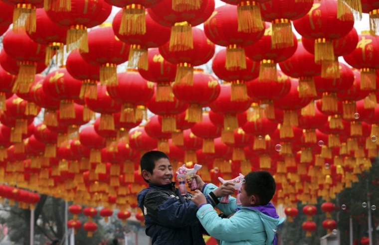 Children play with bubble toy guns under Chinese lunar New Year decorations at a park in Beijing, January 24, 2014. According to the Chinese lunar calendar, the Chinese New Year, which welcomes the year of the horse, falls on January 31. (REUTERS/China Daily)