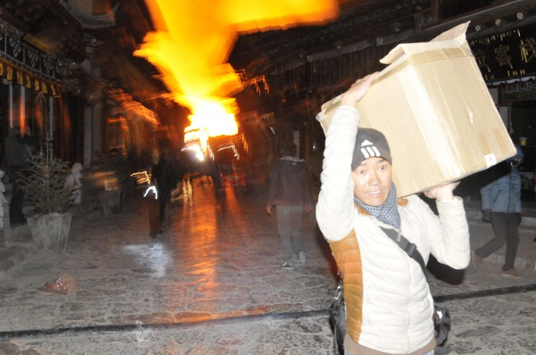 A man carrying his belongings, runs away from a fire at the Dukezong Ancient Town in Shangri-la county, Yunnan province January 11, 2014. More than 1,000 people were battling the fire that broke out early Saturday at a resort county in southwest China's Yunnan province. Residents of the town were evacuated and no casualty has been reported at the moment, according to Xinhua News Agency. (REUTERS/Stringer)