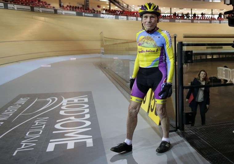 French cyclist Robert Marchand, aged 102, walks onto the track at the indoor Velodrome National in Montigny-les-Bretonneux, southwest of Paris January 31, 2014. Marchand set a new record, cycling 26.98 kms in one hour, in the Masters + 100 category established by the International Cycling Union (UCI). (REUTERS/Jacky Naegelen )