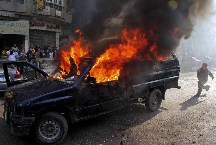 Protesters who support ousted President Mohamed Mursi, set a police vehicle on fire during clashes with riot police at Nasr City district in Cairo January 10, 2014. (REUTERS/Al Youm Al Saabi Newspaper)