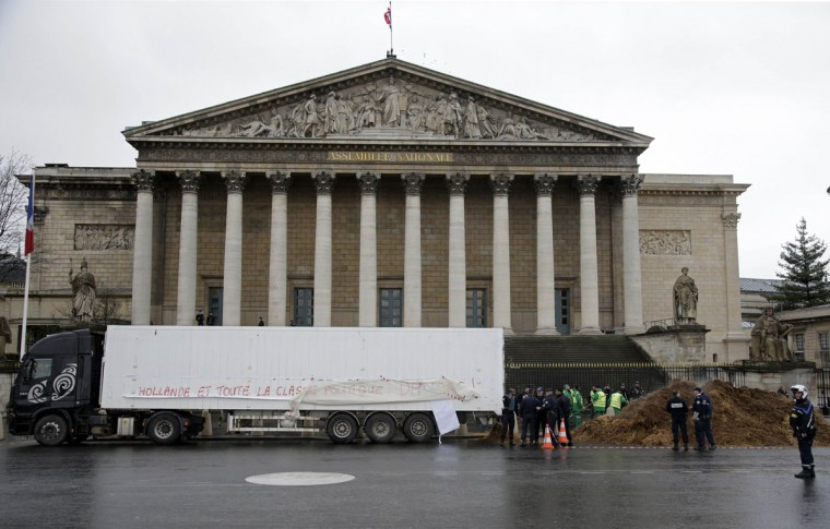 "French police stand guard near a lorry (L) that displays a banner reading, ""Out with Hollande and all politicians. Long Live the VIth Republic"" and a large pile of manure (R) in front of the National Assembly in Paris, January 16, 2014. A man driving a lorry with the protest banner dumped several tonnes of manure in front of the National Assembly in central Paris before police stopped his protest action that targets current President Francois Hollande, politicians in general, and the Fifth Republic. (REUTERS/Jacky Naegelen)"