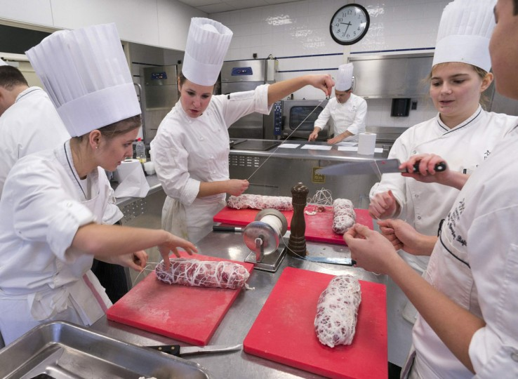 Students prepare shoulders of lamb in a kitchen during a class by French chef Eric Cros (C Rear) at the Institut Paul Bocuse, in a 19th century chateau, in Ecully near Lyon, December 11, 2013. The Institut Paul Bocuse, created by French chef Paul Bocuse in 2004, trains students in every aspect of the culinary arts and hotel and restaurant management, on the path to Excellence. The cooking school welcomes 450 students from 37 countries each year for a unique immersion in French gastronomic heritage. Picture taken December 11, 2013. (REUTERS/Robert Pratta)