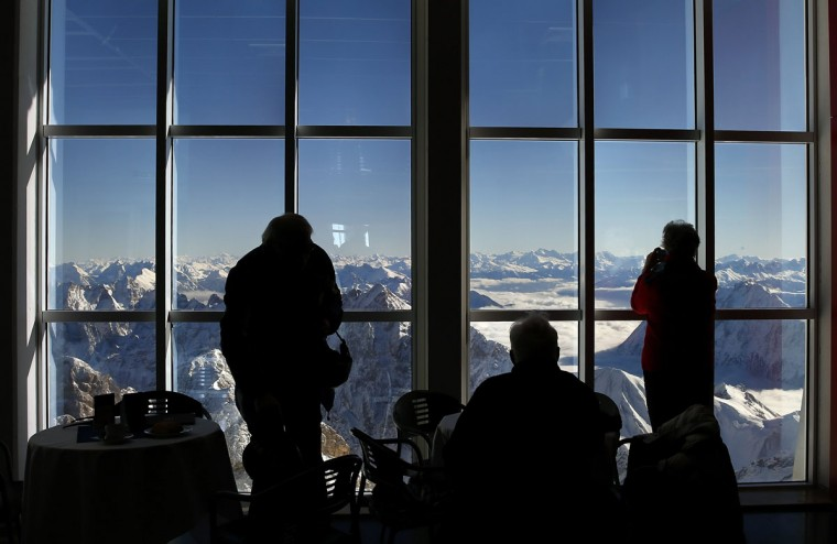 Visitors are silhouetted against a window of a restaurant as they look out at the snow covered mountain summits from Germany's highest mountain the 2,962 metre (9,718 feet) Zugspitze, on a sunny day in the Bavarian village of Grainau January 22, 2014. (REUTERS/Michael Dalder)