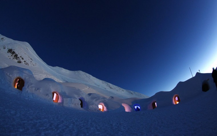 Dimmed lights are switched on in igloos on top of the mountain Nebelhorn, alpine upland, near the southern Bavarian town of Oberstdorf December 30, 2013. The Igloo village of 11 igloos which includes a bar igloo, a dining area igloo and an outside whirlpool with 40 degree hot water, is open during the winter months until April. One night costs 114 euros per person, with breakfast and cheese fondue inclusive. Picture taken December 30, 2013. (REUTERS/Michaela Rehle)