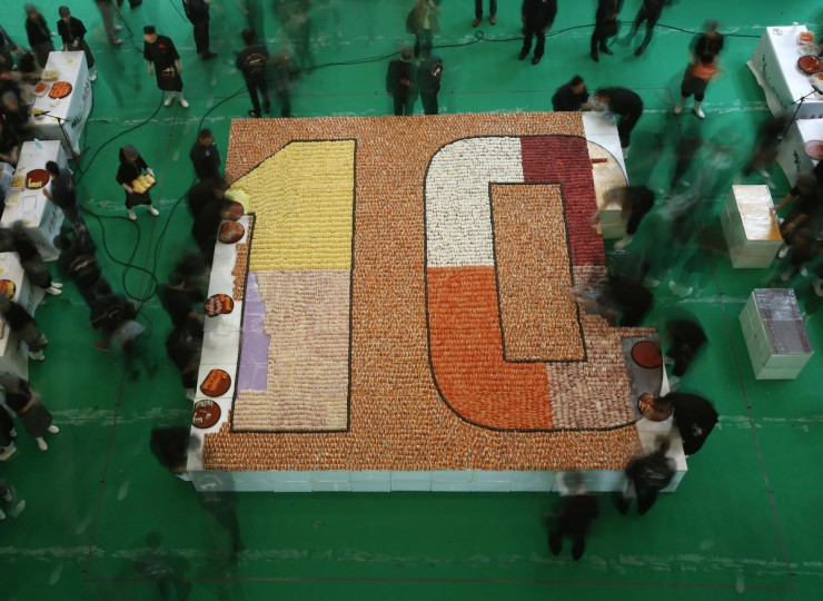Participants arrange sushi to create the largest sushi mosaic in an attempt to break the Guinness World Records during the 10th anniversary of a sushi chain store in Hong Kong. A total of 20,647 sushi pieces were used for a 37-square-metre space to break the record on Wednesday, which was verified and announced by the Guinness World Records at the end of the event. (Bobby Yip/Reuters)