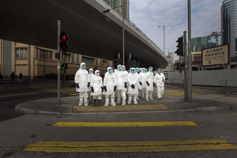 Health officers in full protective gear wait to cross a road near a wholesale poultry market in Hong Kong January 28, 2014. Hong Kong began culling 20,000 chickens and suspended imports of fresh poultry from mainland China for 21 days on Tuesday after the discovery of the H7N9 bird flu virus in a batch of live chicken from the southern province of Guangdong (Tyrone Siu/Reuters)
