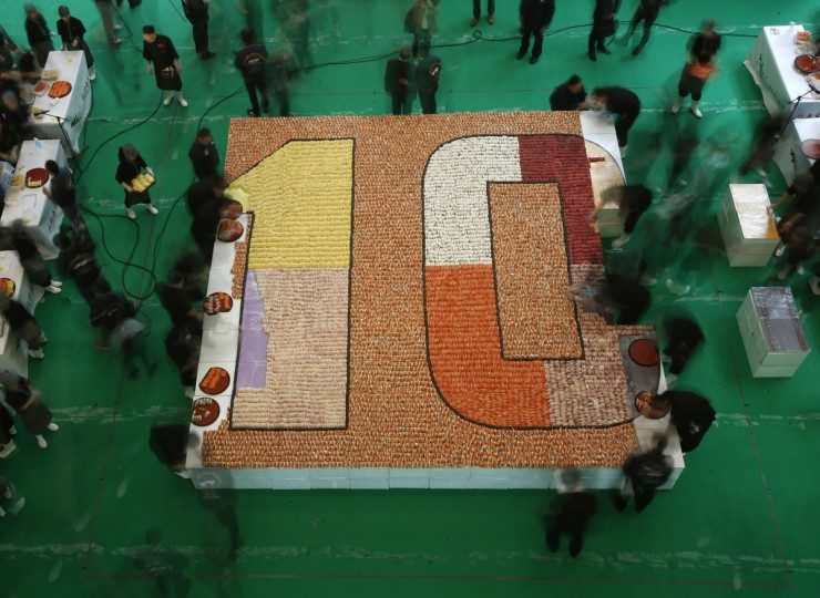 Participants arrange sushi to create the largest sushi mosaic in an attempt to break the Guinness World Records during the 10th anniversary of a sushi chain store in Hong Kong January 8, 2014. A total of 20,647 sushi pieces were used for a 37-square-metre space to break the record on Wednesday, which was verified and announced by the Guinness World Records at the end of the event. (REUTERS/Bobby Yip )