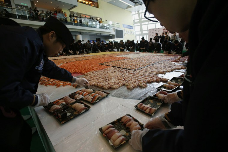 Participants pack sushi to be distributed for free to the public after breaking the Guinness World Records by creating the largest sushi mosaic during the 10th anniversary of a sushi chain store in Hong Kong January 8, 2014. A total of 20,647 sushi pieces were used for a 37-square-metre space to break the record on Wednesday, which was verified and announced by the Guinness World Records at the end of the event. (REUTERS/Bobby Yip)