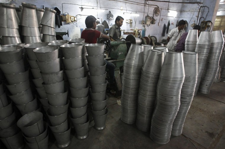 Employees work inside a steel bucket manufacturing unit at an industrial area on the outskirts of the western Indian city of Ahmedabad January 2, 2014. India's factories lost momentum last month as softness in new domestic orders prompted firms to lower production growth, but demand from abroad picked up, a survey showed on Thursday. (REUTERS/Amit Dave)