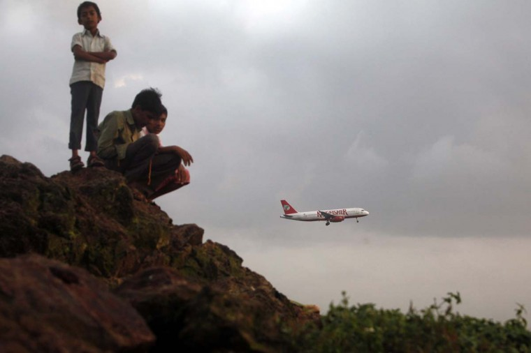 Hunger strike: People gather on top of a hill overlooking Chhatrapati Shivaji International Airport as an Airbus A320 aircraft of Indian carrier Kingfisher Airlines comes in to land in a 2012 file photo. Employees of the defaulting company made plans last week to start a hunger strike today after going unpaid for 17 months, according to Indian media site bhaskar.com. (REUTERS/Vivek Prakash)