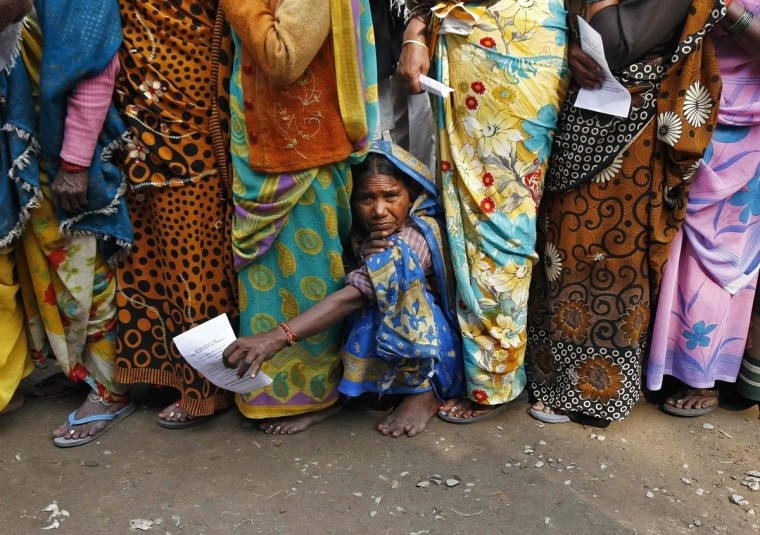 "Hindu pilgrims wait in line for an eye check up at a camp organised by a non-governmental organisation (NGO) before heading for an annual trip to Sagar Island for the one-day festival of ""Makar Sankranti"", in Kolkata January 11, 2014. Hindu monks and pilgrims are making the annual trip to Sagar Island for a holy dip at the confluence of the Ganges river and the Bay of Bengal on January 14 (REUTERS/Rupak De Chowdhuri)"