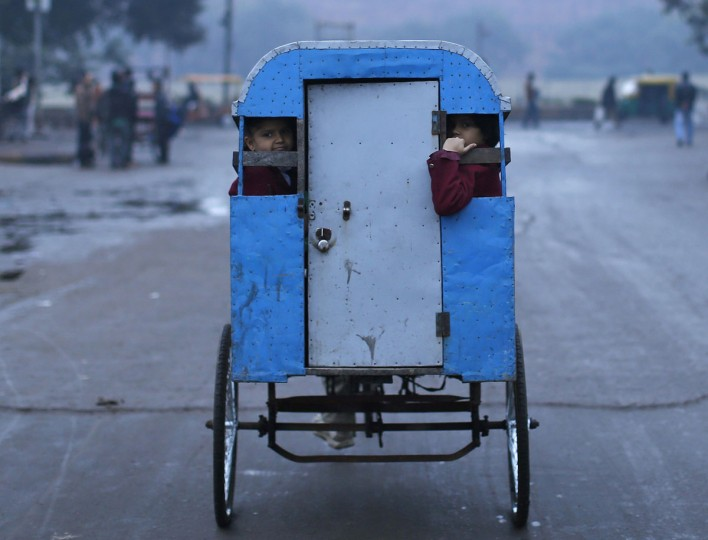 Schoolchildren travel to their school in a cycle rickshaw on a cold morning in the old quarters of Delhi January 22, 2014. (REUTERS/Ahmad Masood)